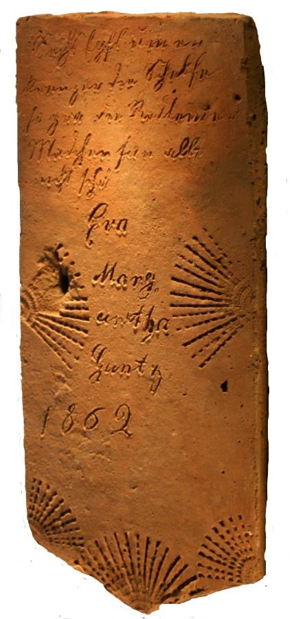 """Spruchziegel; Aufschrift: """"Sechs epfl um en Kreuzer der Schale so grä die Redlemer Mädchen san alle nicht sche(ö)n G.M.Ganz 1862""""; Reichsrot / Tauber"""